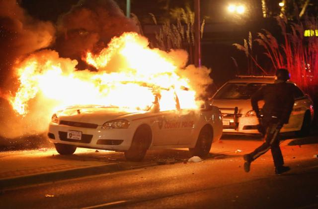 Rioter runs beside a torched police car, Ferguson